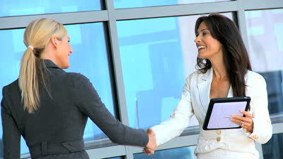 Stock-footage-two-city-businesswomen-meeting-up-using-a-wireless-tablet-outside-modern-office-workplace